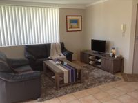 Open plan living with ceiling fan, TV and DVD player
