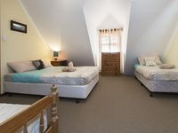 Bedroom three upstairs has 1x Queen bed and 2x Single beds