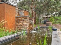Water feature with BBQ area in background