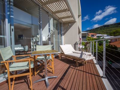 Large balcony with sunloungers, table + chairs and views to Illawarra Escarpment