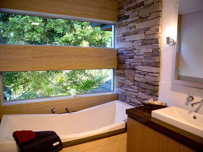 The ensuite bathtub has soothing leafy views, and is oh so comfortable