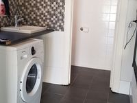2nd bathroom with private toilet and a front load washing machine