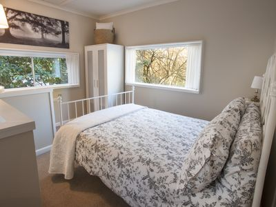 Dovecote Cottage - Bedroom with double bed, 3 windows looking over camellia tree