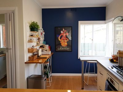 Open plan kitchen, with supplies and utensils. Washing machine and laundry