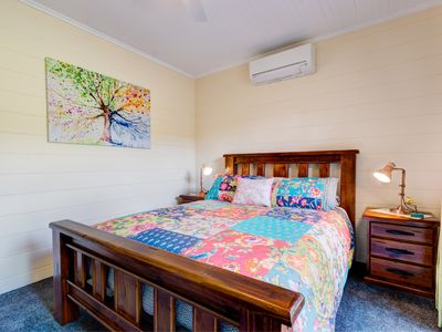 Cosy bedroom containing queen size bed, aircon, ceiling fan & wardrobe space