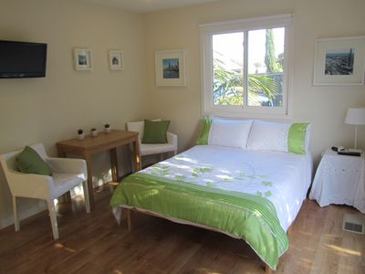 Lovely light room with double bed, table and chairs, TV