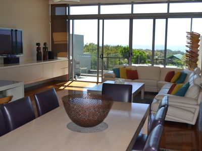 The open plan living area has views of the ocean over the native bush