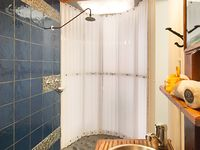 The shower has a copper shower rose and is tiled with river rocks