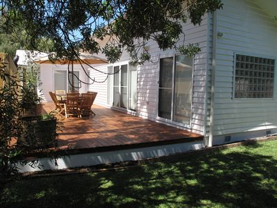 Lush garden surrounds large rear deck that is drenched in sunshine