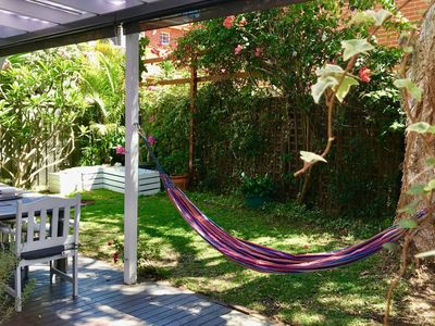 Great outdoor area with dining table, fire pit and hammock