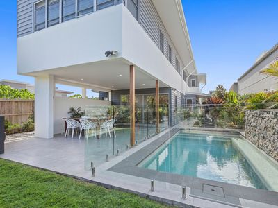 Sparkling swimming pool in beachfront yard by covered alfresco entertaining area