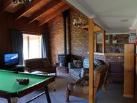 Lounge room with combustion heater and pool table