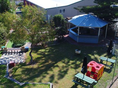 View towards the street of gazebo, BBQ, dog pen, Minigolf and outdoor chess.
