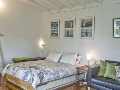 Bed-living space with leather sofa, original art
