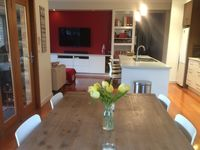 Meals area with bifold doors opening to deck with BBQ & outdoor dining setting