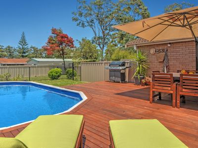 Expansive back deck and pool with sunloungers and outdoor table and chairs
