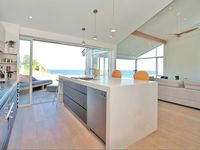 Large caesar stone bench in open plan kitchen with fully reclining glass doors