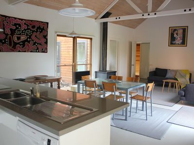 Open plan kitchen, dining and loungeroom, TV, with courtyard and garden views