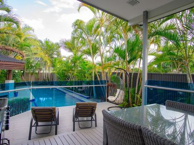 Covered alfresco dining area and sun deck overlook stunning 12 mt pool & cabana