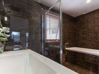 The Pool House bathroom features Italian marble, spa bath and large shower.