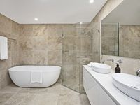 The main bathroom has a luxurious bath and twin basins