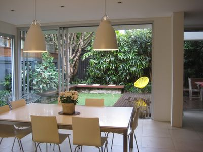 Large open plan dining area overlooking tropical garden and undercovered BBQ