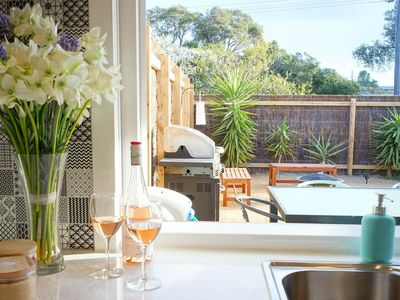 Overlooking the private yard through serving window from a fully equiped kitchen