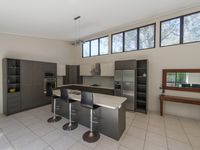 Full sized, modern kitchen with stovetop, oven and large fridge